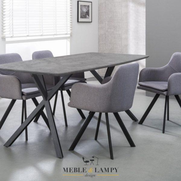 Efektownie wykończony stół wykonany z połączenia płyty okleinowej i stali. Owalny blat o wymiarach 160 x 90 cm wykonany jest z płyty pokrytej okleiną 3D betonowy/szary.